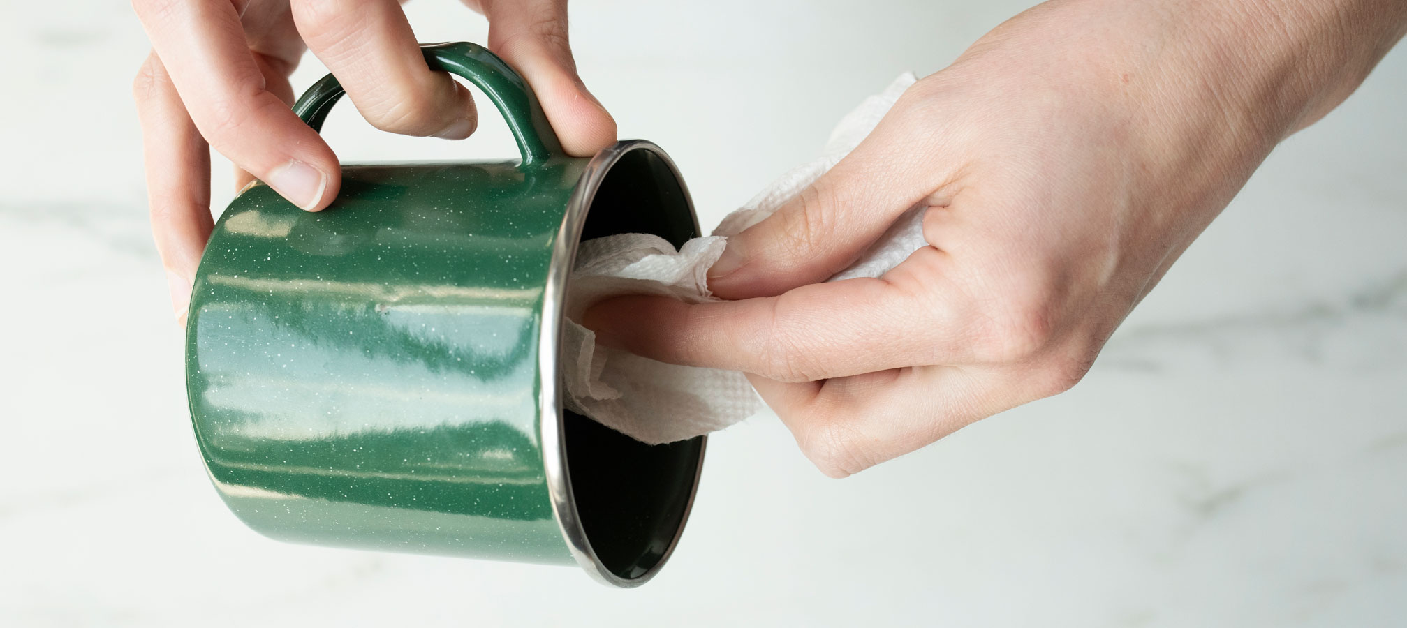 Cleaning out enamel camping mug to prepare for candle making