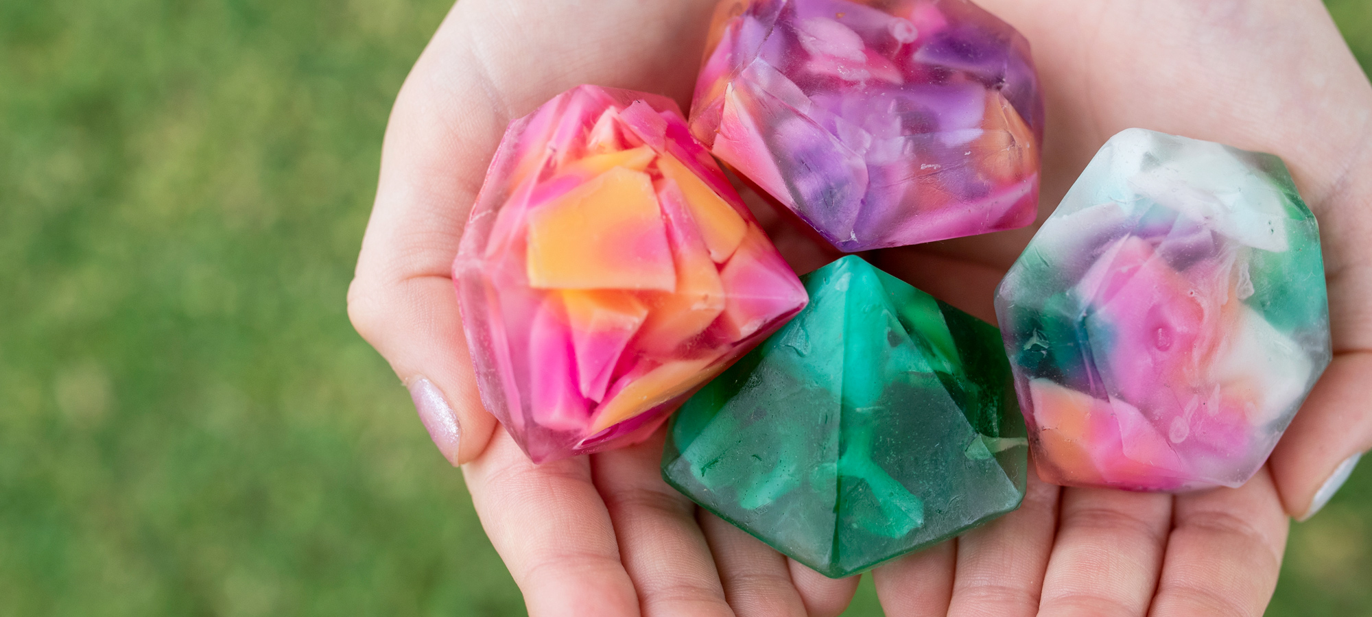Hands holding colorful diamond shaped hand soaps