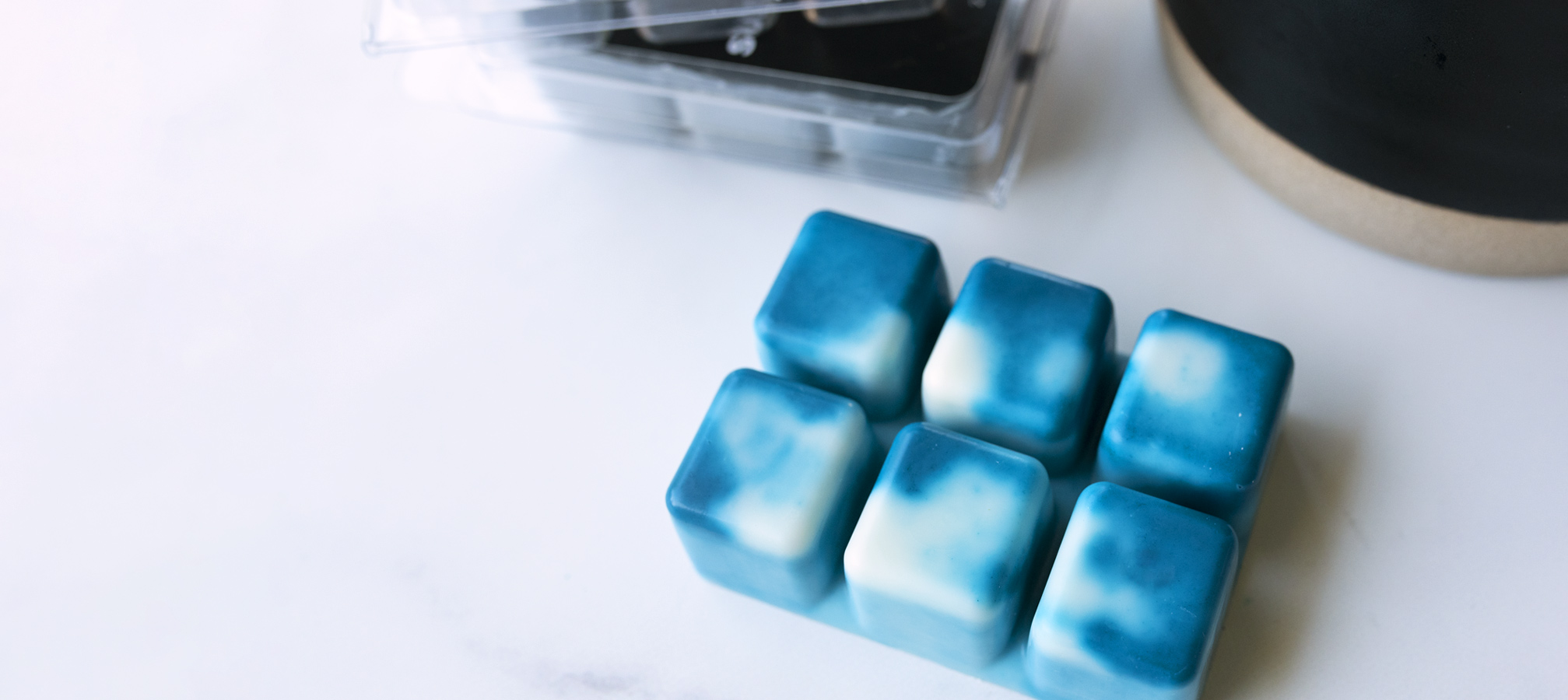 Teal and white marbled wax melt on counter.