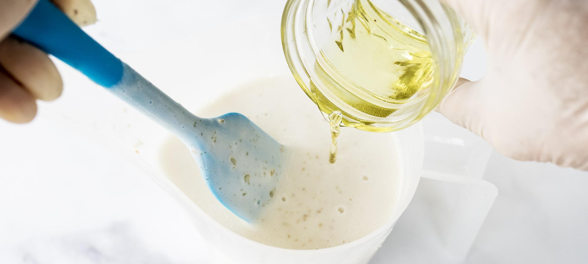 Adding fragrance oil to oatmeal shea soap base.