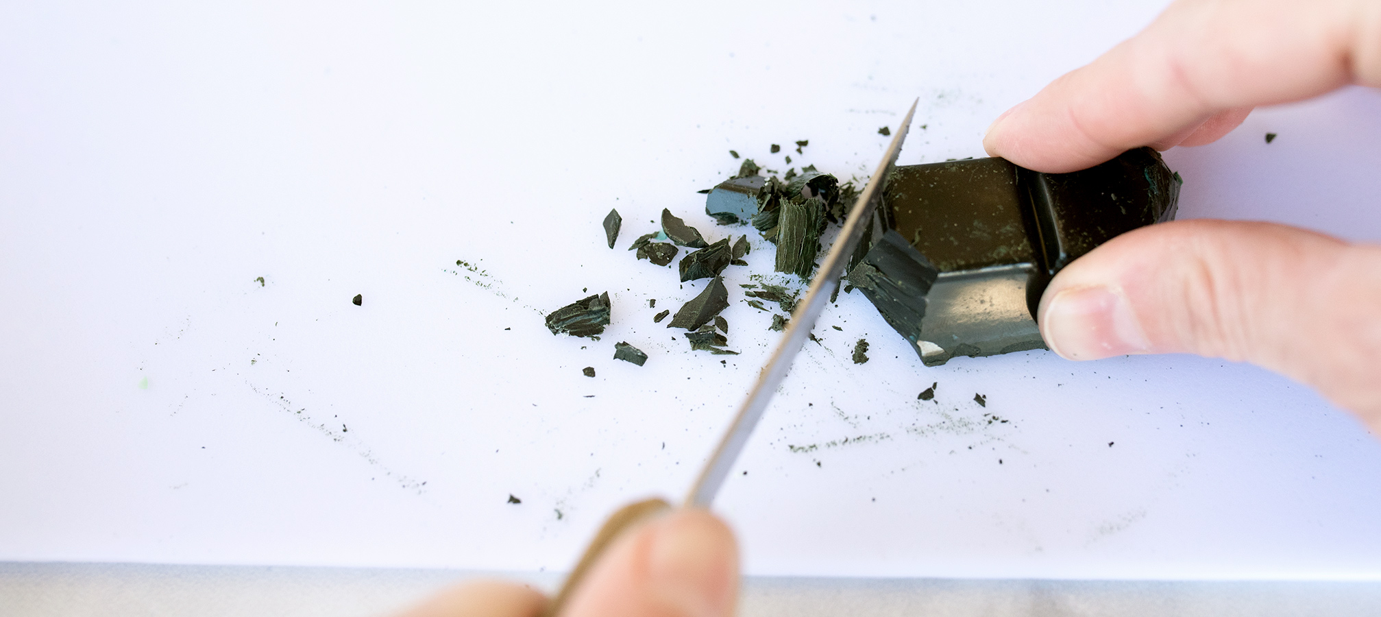 Shaving pieces of a Forest Green Dye Block on a cutting board.